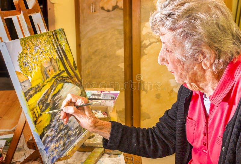 Pintura mayor de la mujer en su caballete, en su estudio en Francia fotografía de archivo