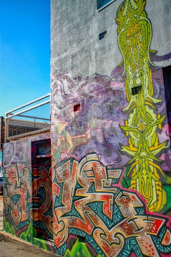 Pintura mural colorida dos grafittis no lado da parede foto de stock