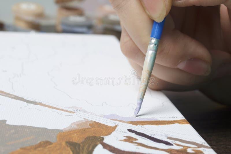 Pintura na lona por números Uma mulher está guardando uma escova e está tirando-a Recipientes numerados com pinturas e escovas no fotos de stock