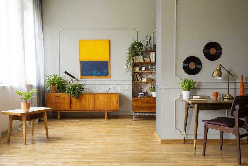Pintura na parede cinzenta acima do armário de madeira no interior do espaço de trabalho com a cadeira na mesa Foto real imagem de stock