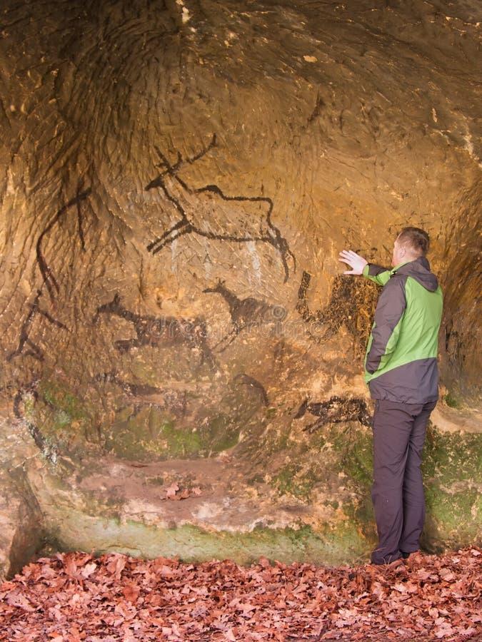 Pintura negra del carbono de la caza humana en la pared de la piedra arenisca, copia de la imagen prehistórica Arte abstracto de  imagenes de archivo