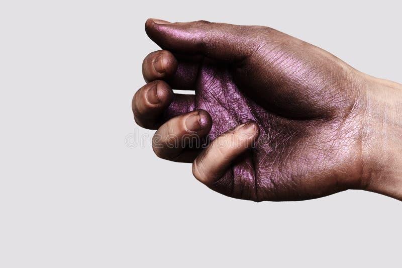 Pintura púrpura brillante en la mano masculina imagenes de archivo