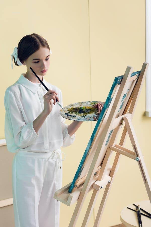pintura pensativa do adolescente na armação com escova foto de stock royalty free