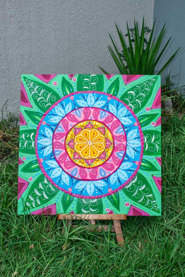 Pintura, pintando una situación de la mandala en un caballete, al aire libre en la hierba, colores brillantes imagenes de archivo