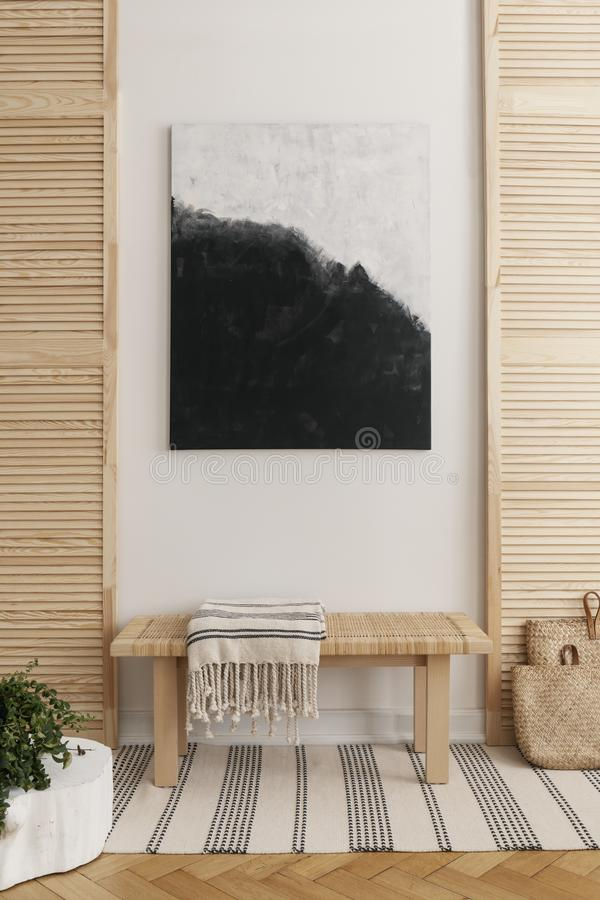 Pintura preto e branco acima do banco de madeira com a cobertura listrada na sala de espera natural, foto real com o modelo na pa fotos de stock