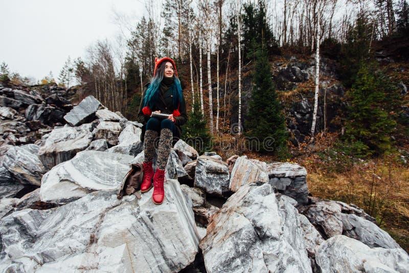 Pintura que se sienta en las rocas en el acantilado, libreta de la muchacha del artista Opinión maravillosa de la caída imágenes de archivo libres de regalías