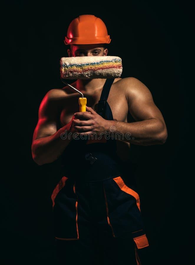 Pintura que su voluntad sea orgullosa de Rodillo del cepillo del control del trabajador en manos musculares Hombre experto del pi fotografía de archivo libre de regalías