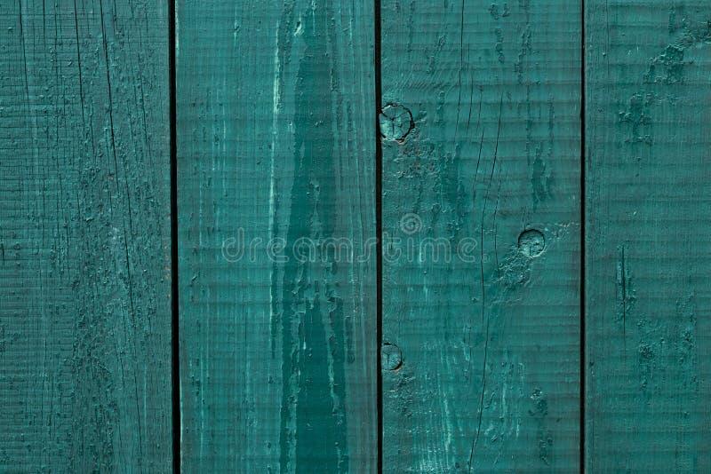 Pintura rachada da cerca de madeira As placas de madeira ásperas pintaram verde Fundo de madeira da textura, cerca da parede da m fotografia de stock royalty free