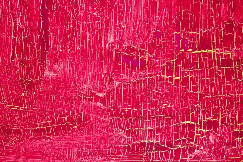 Pintura rosada rojo oscuro agrietada en la superficie amarilla imagenes de archivo