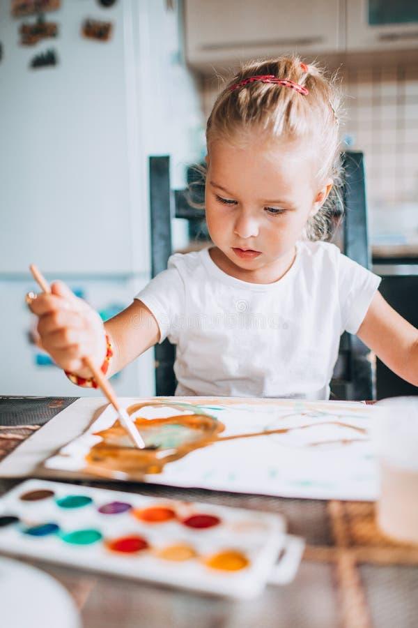 Pintura rubia hermosa de la muchacha con colores de la brocha y de agua en la cocina Concepto de las actividades del ni?o Cierre  foto de archivo libre de regalías