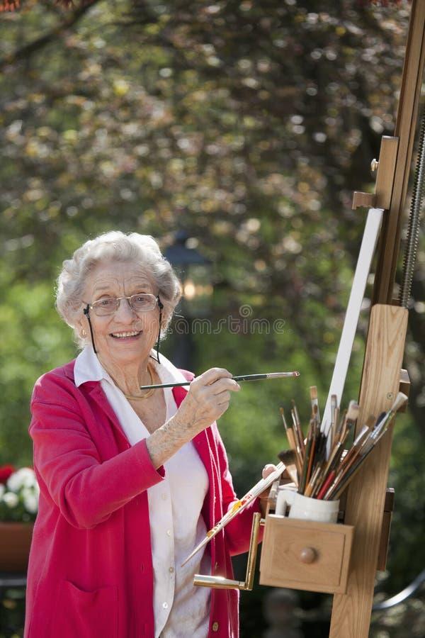 Pintura sênior de sorriso da mulher imagens de stock