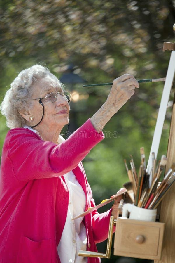 Pintura sênior de sorriso da mulher fotografia de stock