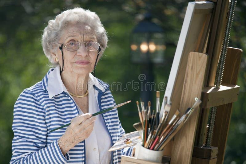 Pintura sênior de sorriso da mulher foto de stock royalty free