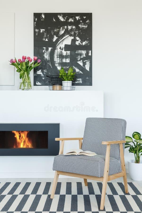 Pintura sobre la chimenea en interior moderno de la sala de estar con la palmadita imagen de archivo libre de regalías