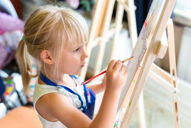 Pintura sonriente rubia linda de la muchacha en el caballete en la lección del taller en el estudio del arte Cepillo de la tenenc foto de archivo libre de regalías