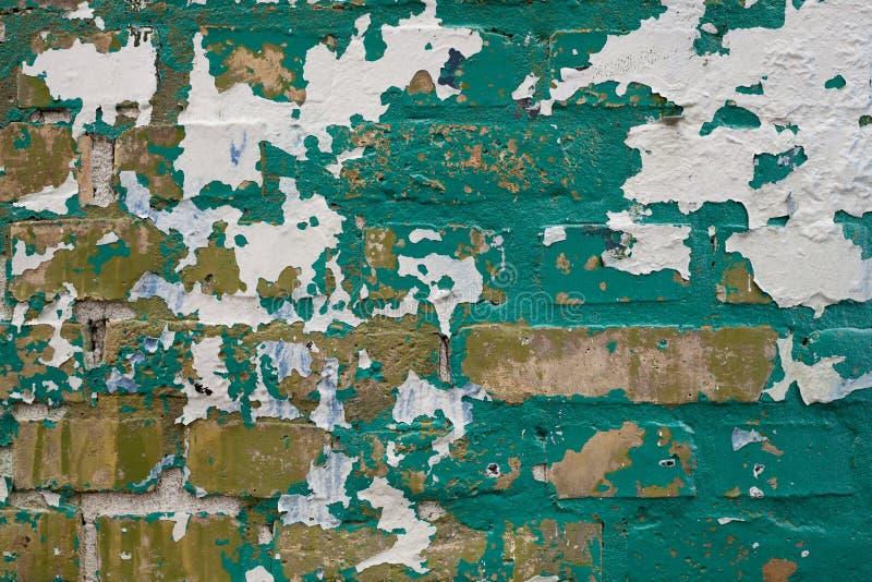 Pintura verde e branca que descasca fora a parede de tijolo amarela fotografia de stock royalty free