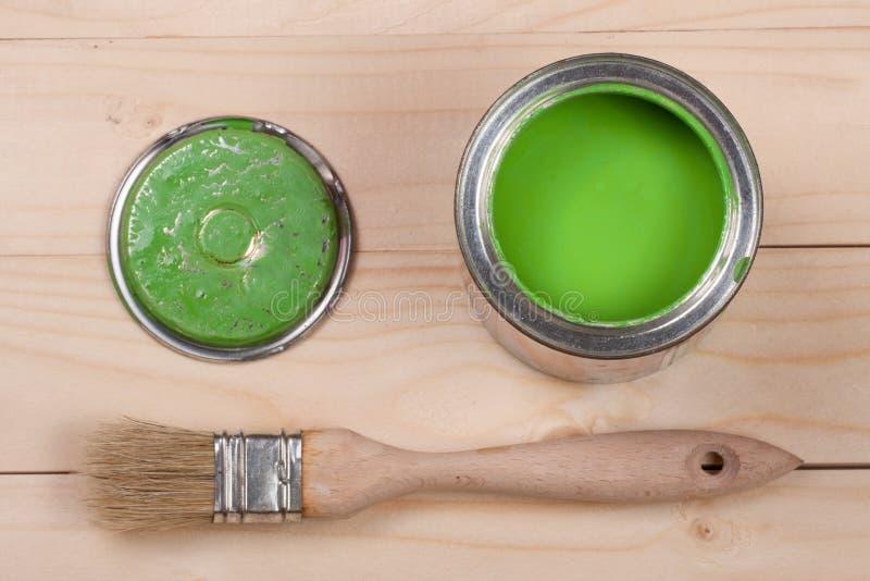 Pintura verde no banco a reparar e escovar no fundo de madeira claro fotografia de stock
