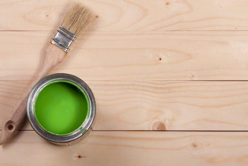 Pintura verde no banco a reparar e escovar no fundo de madeira claro com espaço da cópia para seu texto Vista superior imagens de stock