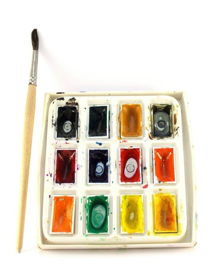 Pintura y brocha coloreadas en blanco fotos de archivo