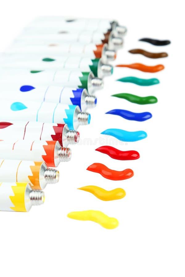 Pinturas acrílicas coloridas en tubos en el fondo blanco fotos de archivo