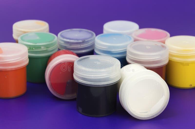 Pinturas coloreadas del aguazo sobre fondo púrpura fotos de archivo