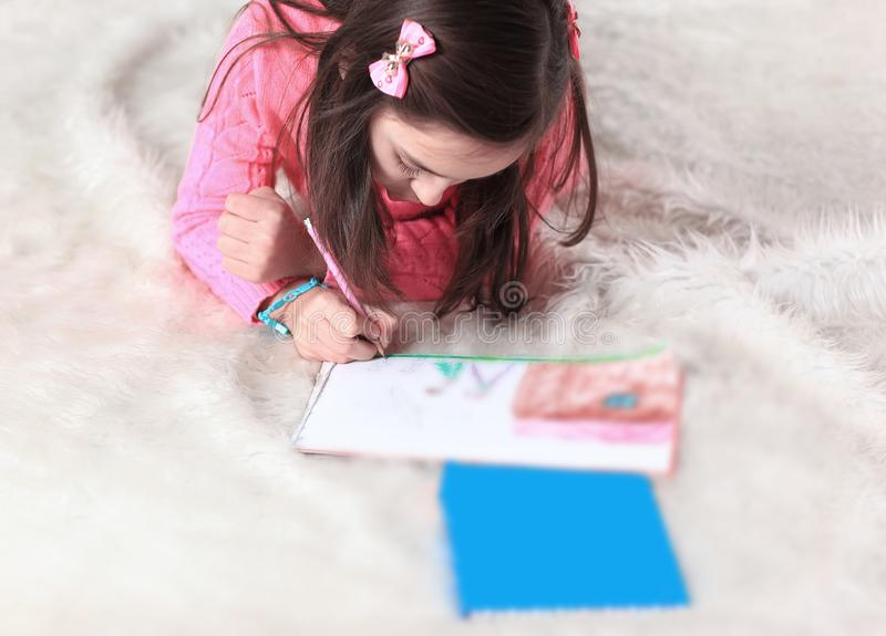 Pinturas da menina com os lápis, encontrando-se no assoalho na sala de visitas imagem de stock