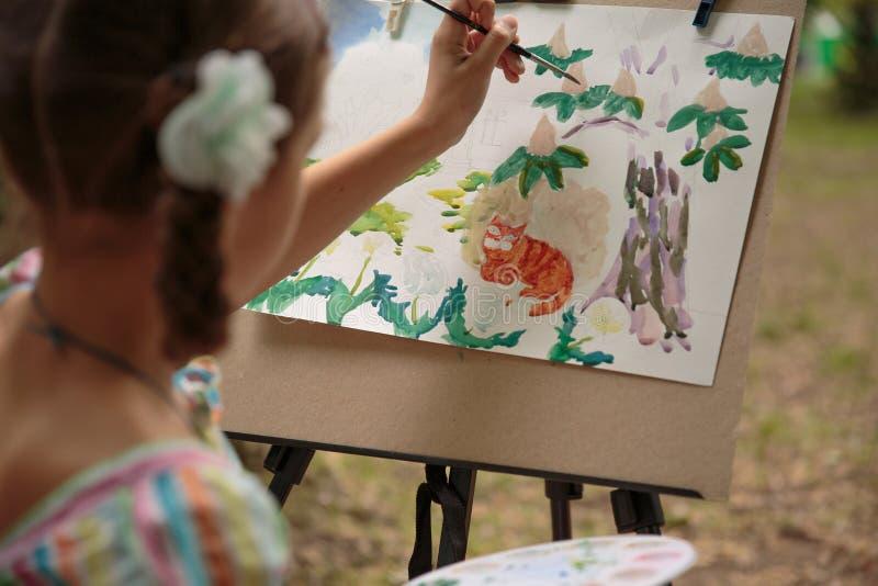 Pinturas da menina em uma armação na lição do desenho imagem de stock royalty free