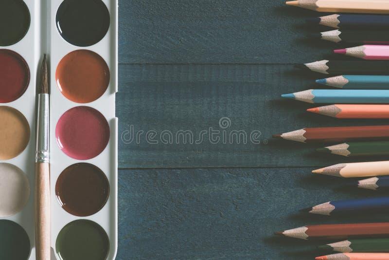 Pinturas de la acuarela del fondo con un cepillo y mentira delante de los lápices coloreados en un escritorio de madera de la esc imagenes de archivo