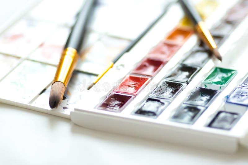 Pinturas de la acuarela fijadas, paleta y cepillos foto de archivo