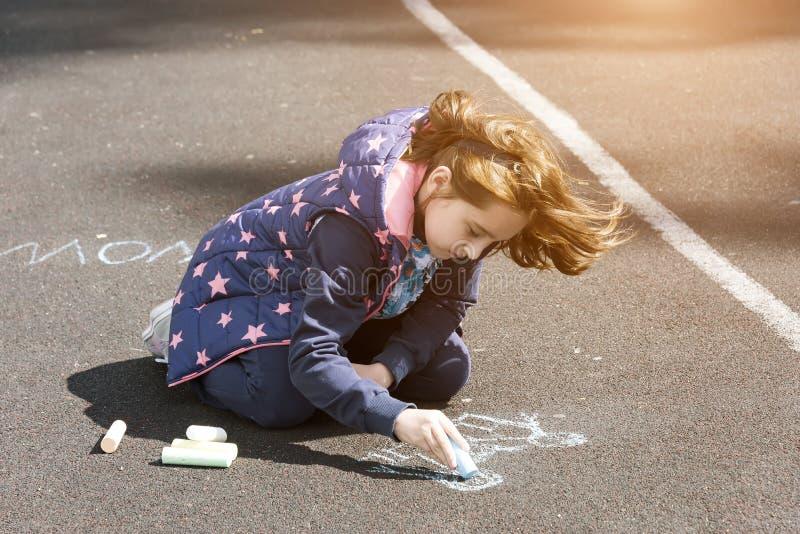 Pinturas del niño con tiza en el asfalto fotos de archivo
