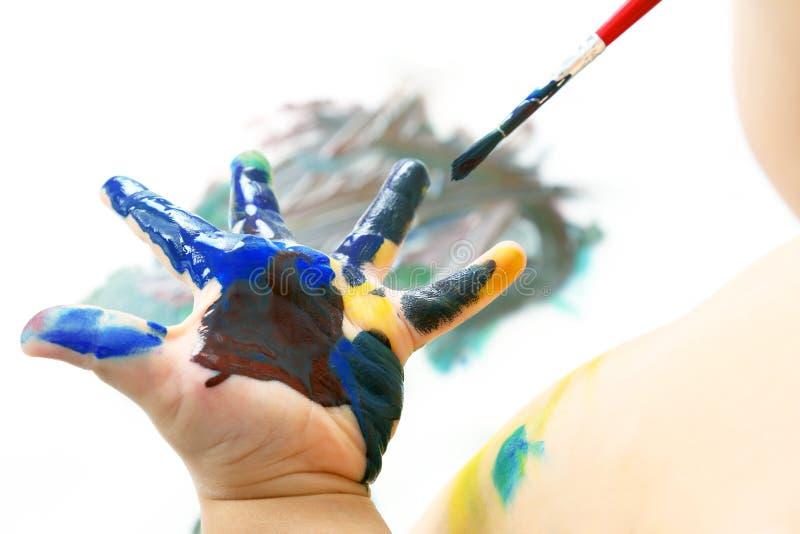 Pinturas del ni?o con la pintura su mano creatividad y afici?n art?stica fotografía de archivo libre de regalías
