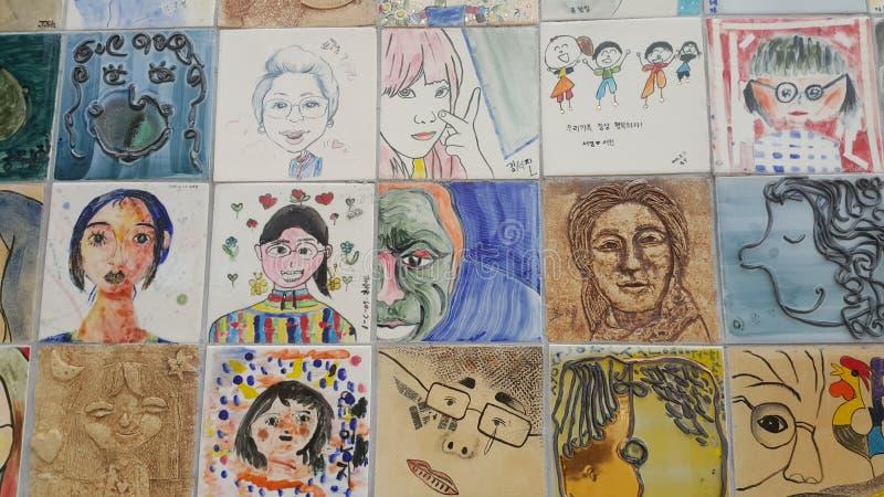 Pinturas e caras esculpidas dos povos na parede para a mem?ria fotos de stock