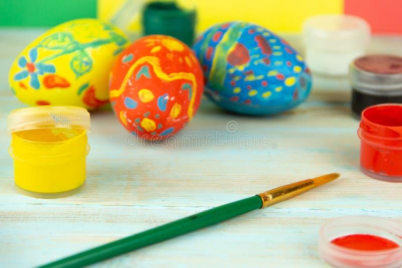 Pinturas e escova do close-up no fundo de madeira multicolorido com crufts da Páscoa dos ovos da páscoa imagens de stock