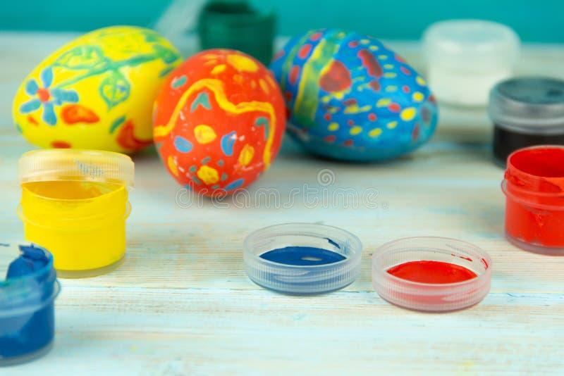 Pinturas e ovos da páscoa do close-up no fundo de madeira multicolorido com crufts da Páscoa dos ovos da páscoa imagem de stock