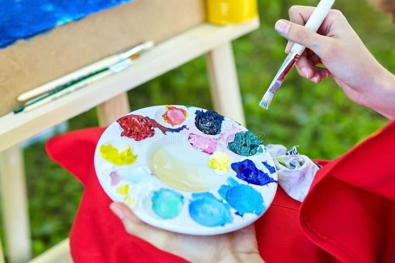 Pinturas, escova, paleta, mão fêmea do artista foto de stock royalty free