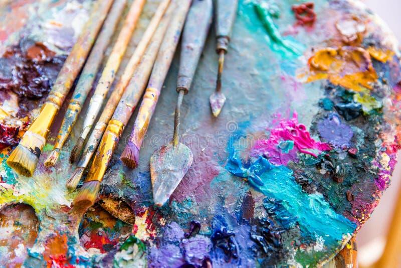 Pinturas misturadas brilhantes da cor na paleta da arte com pincéis foto de stock