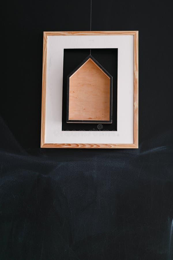 Pinturas quadradas modernas simples com a casa de madeira que pendura na parede preta crua imagens de stock