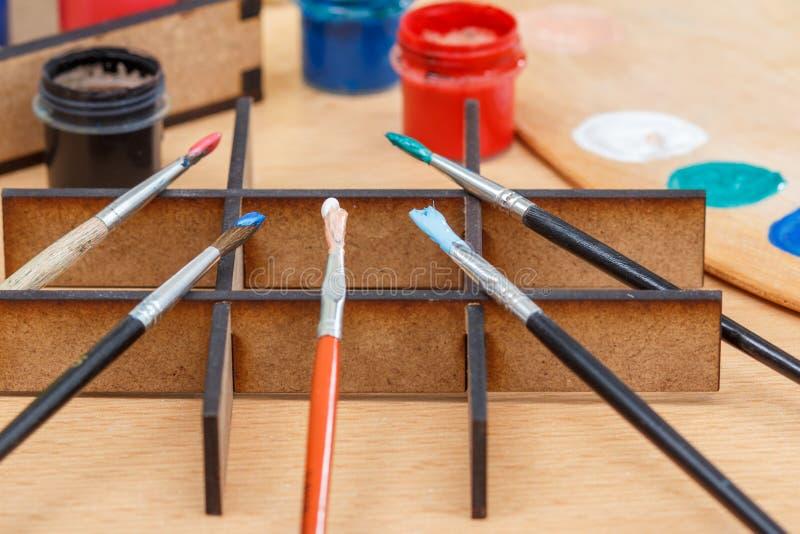Pinturas y cepillos coloridos en un soporte de madera listo para pintar fotografía de archivo libre de regalías