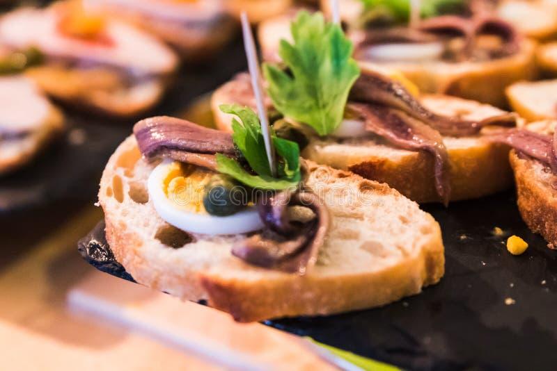 Pintxos da anchova com ovo cozido e alcaparras Os tapas espanh?is chamaram pintxos do pa?s Basque fotos de stock