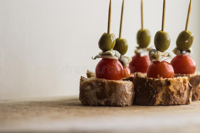 Pintxos Pintxo set, olive, anchovy, cherry tomato and bread on a Rustic Board, food from the Basque Country stock photo