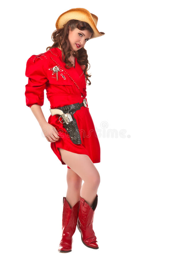 Pinup Cowgirl. Cowgirl pinup in vintage red jumper, cowboy hat, cowboy boots and six shooter stock photo