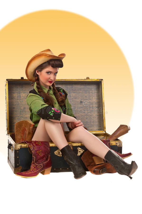 Pinup Cowgirl Package. Cowgirl pinup in vintage western shirt, cowboy hat, cowboy boots and sitting in a trunk of boots royalty free stock images