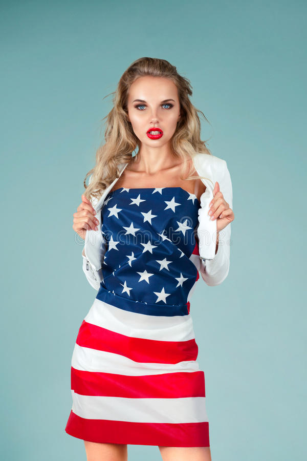 Pinup girl with american flag. Beautiful pin-up style fashion model in dress made from american flag stock image