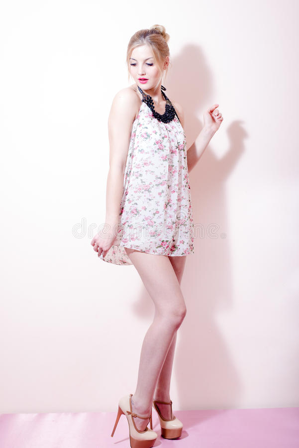 Pinup girl beautiful young attractive blond woman in a dress and high heels shoes stock photography