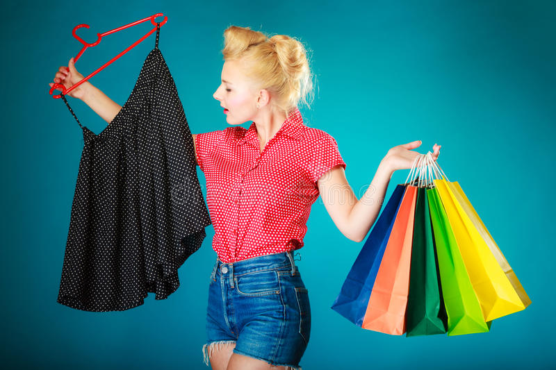 Pinup girl buying clothes black skirt. Sale retail stock photography