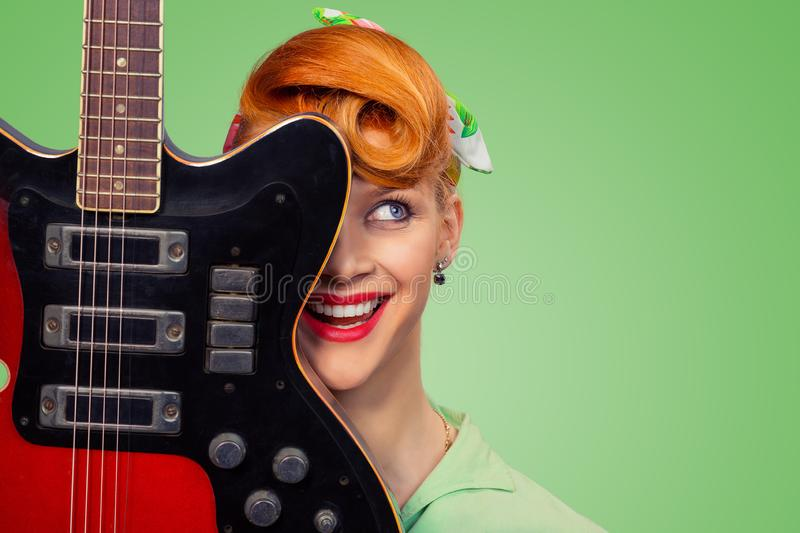 Pinup girl with electric acoustic rock guitar smiling royalty free stock image
