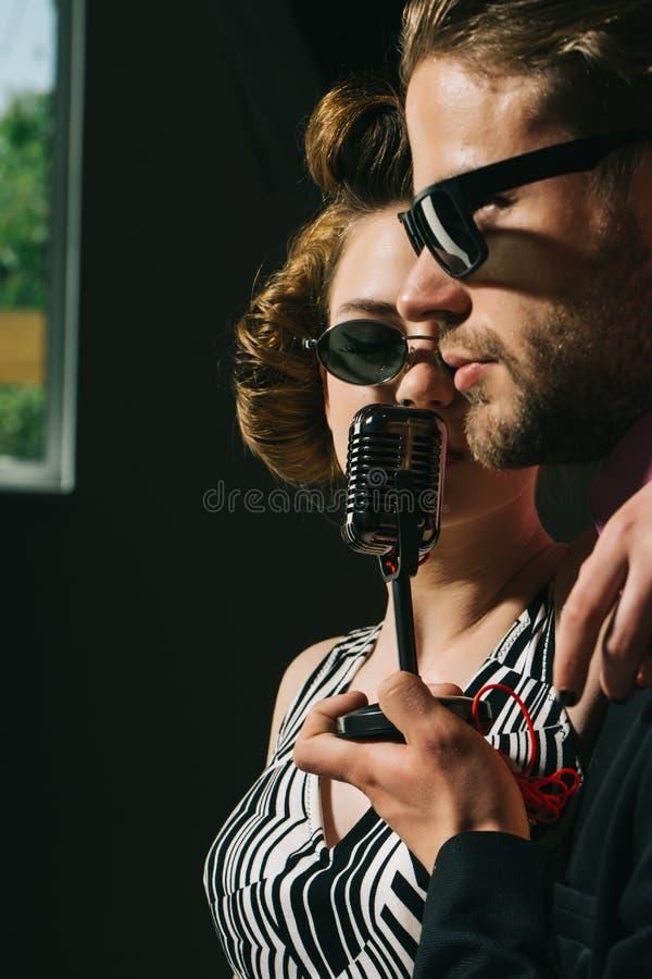 Pinup girl and man sing karaoke, radio. stock photos