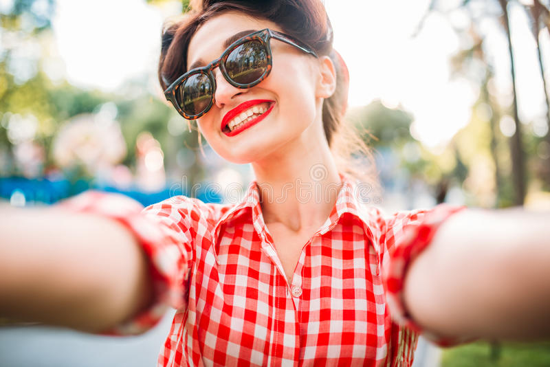 Pinup girl selfie shot outdoors, fifties fashion. Pinup girl in sunglasses, selfie shot outdoors, fifties american fashion. Attractive model in pin up style stock images