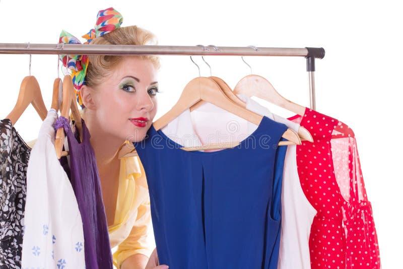 Pinup kobieta pokazuje ona suknie na wieszaku fotografia royalty free