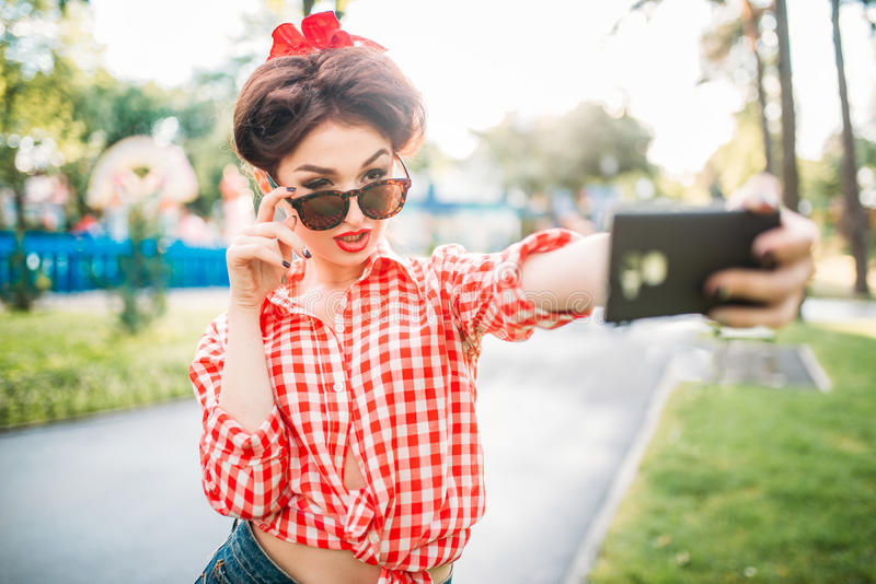Pinup lady makes selfie on camera in park. Pinup lady makes selfie on phone camera in park, fifties american fashion. Attractive model in pin up style stock photos